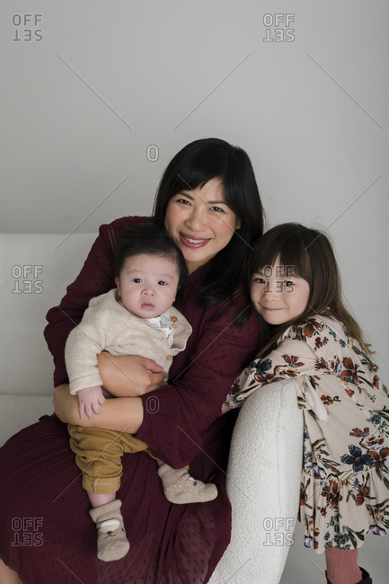 Portrait of an Asian woman sitting on white couch with her baby boy and daughter