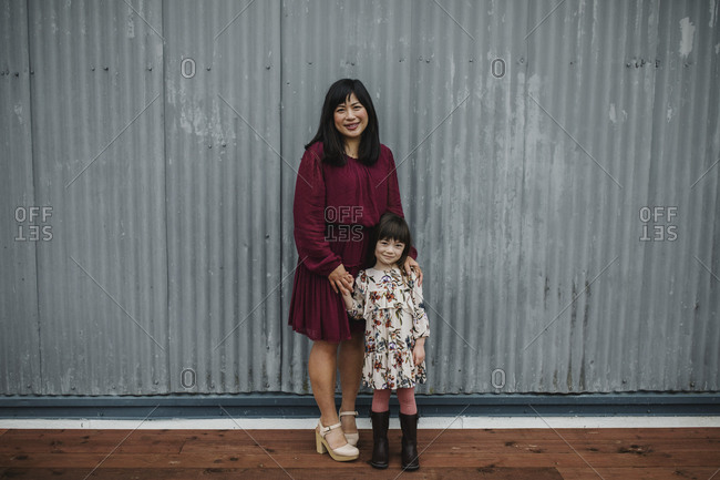 Mom and daughter standing in front of a corrugated metal wall