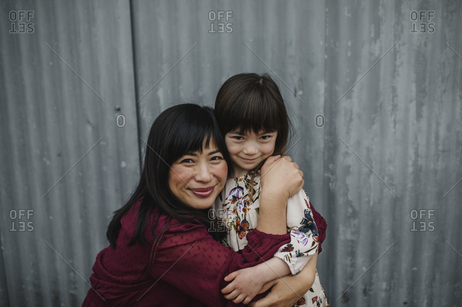 Mom and daughter embracing in front of a corrugated metal wall