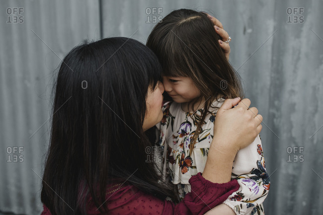 Mom kissing daughter in front of a corrugated metal wall