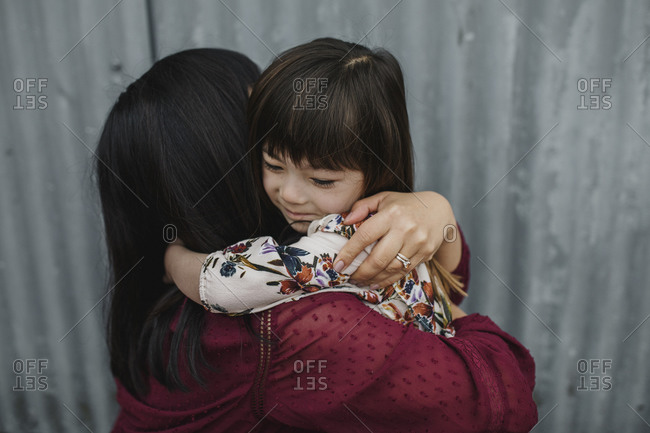 Mom and daughter hugging in front of a corrugated metal wall