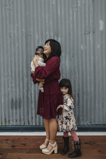 Mother holding baby and standing by daughter in front of a corrugated metal wall