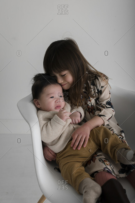 Portrait of a young girl snuggling with baby brother on a white chair