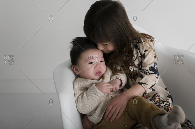 Young girl comforting her baby brother on a white chair