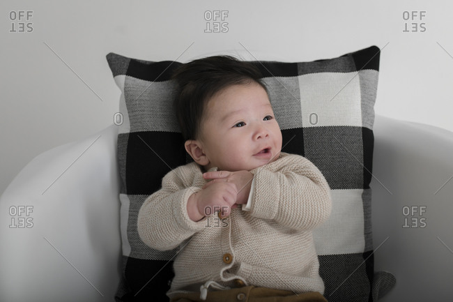 Portrait of an adorable baby boy in a cardigan looking away