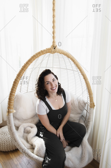 Woman sitting in chair swing with bright windows behind