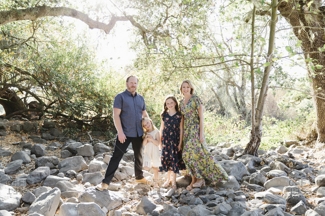 Mom and dad with two young daughters standing on rocks under trees