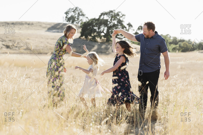 Mom and dad dancing with two young daughters in a wheat field