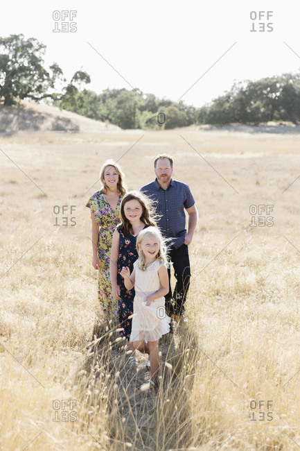 Mom and dad with two young daughters in a wheat field