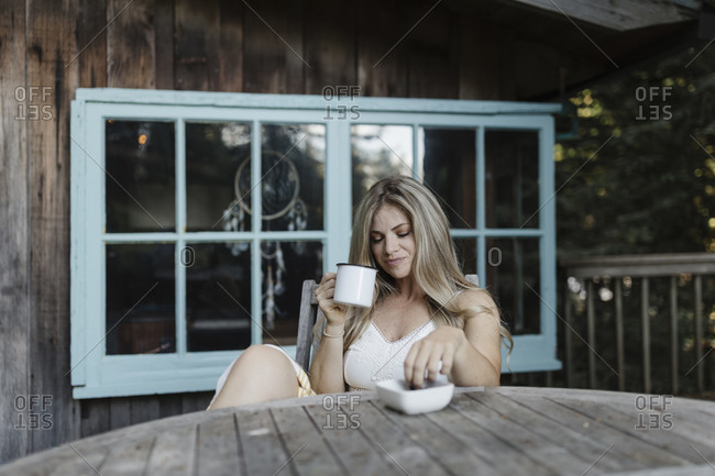 Blonde woman having coffee on deck of a cabin in the woods
