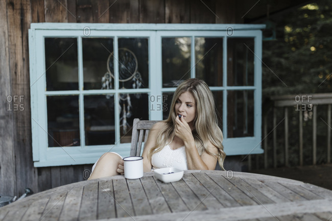 Blonde woman having breakfast on deck of a cabin in the woods