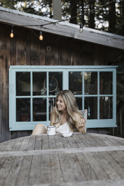 Blonde woman laughing while having coffee on deck of a cabin in the woods