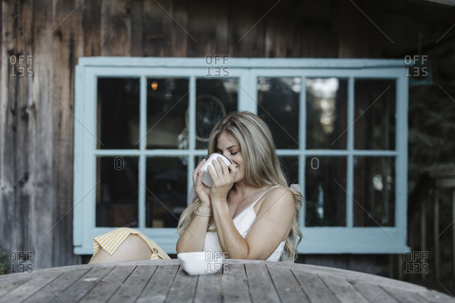 Blonde woman sipping coffee on deck of a cabin in the woods