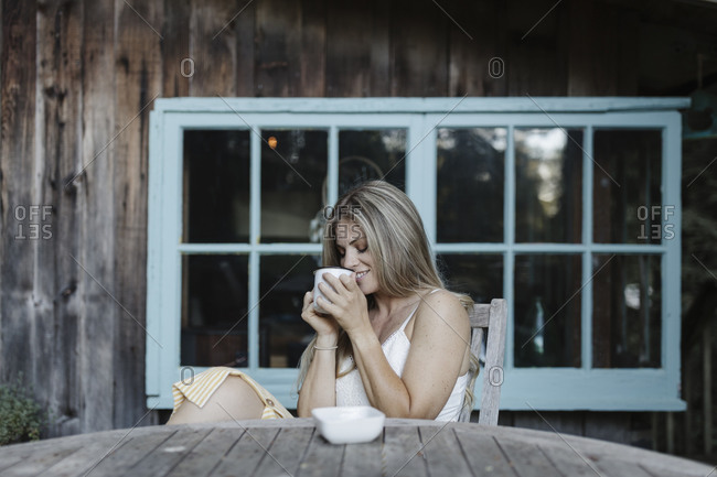 Woman with long blonde hair sipping coffee on deck of a cabin in the woods