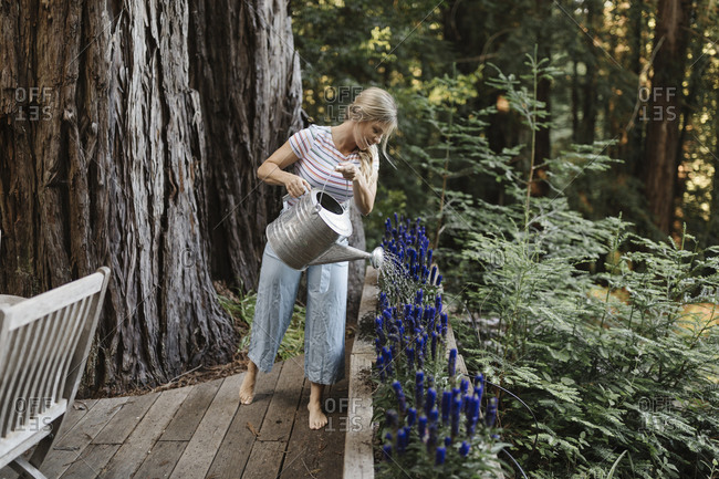 Blonde woman watering plants on deck of a cabin in the woods