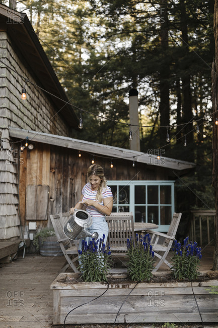 Blonde woman using a watering can to water plants on deck of a cabin in the woods