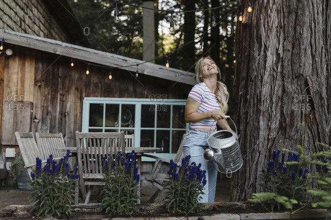Woman using a watering can to water plants on deck of a cabin in the woods and laughing