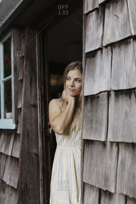 Blonde woman looking out doorway of a cabin