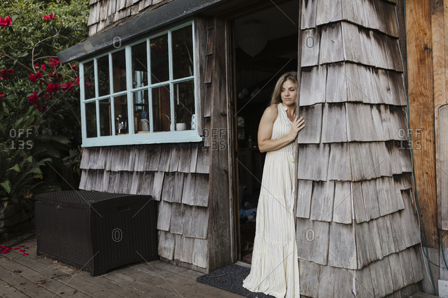 Blonde woman looking out doorway of a cabin in the woods