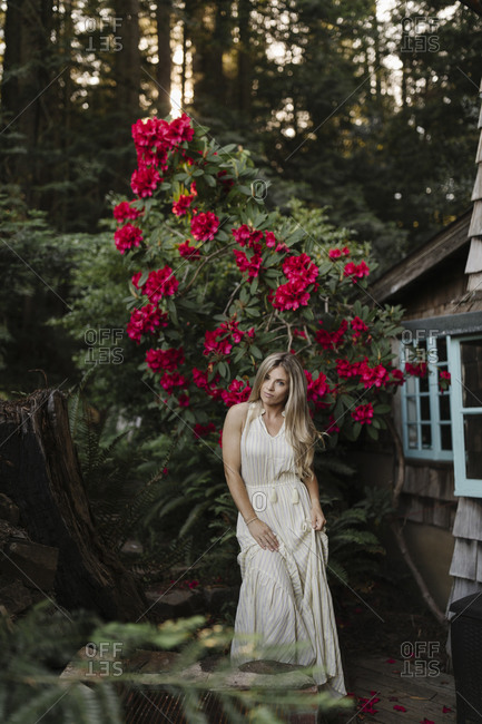 Blonde woman standing in front of a large flowering shrub by a cabin in the woods