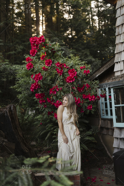 Woman standing in front of a large flowering shrub by a cabin in the woods
