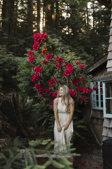 Woman with long blonde hair by a large flowering shrub by a cabin in the woods