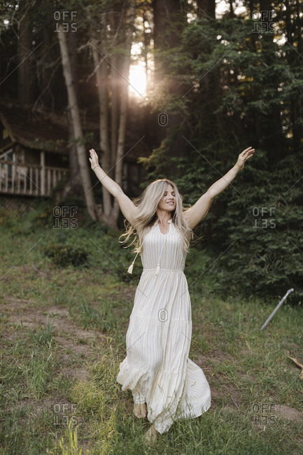 Blonde woman walking downhill from a cabin with her arms in the air