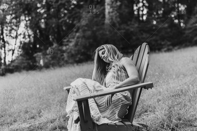 Blonde woman resting in an Adirondack chair in black and white