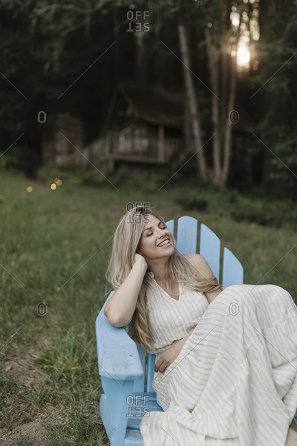 Happy blonde woman resting in an Adirondack chair by a cabin in the woods
