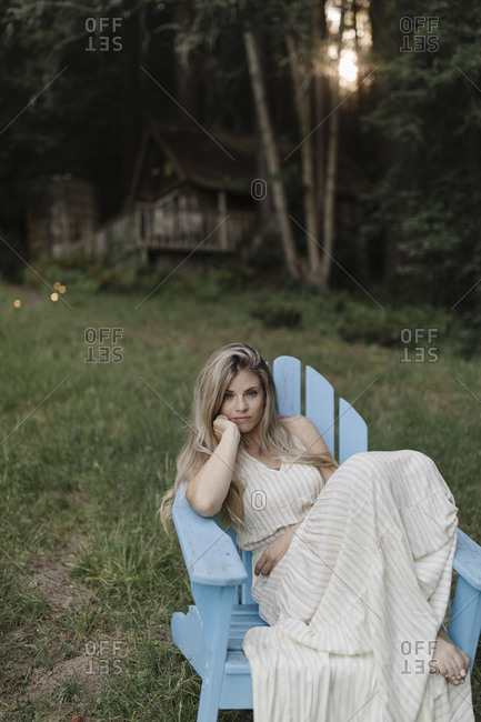 Blonde woman resting in an Adirondack chair by a cabin in the woods