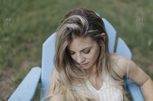 Blonde woman resting in an Adirondack chair looking away