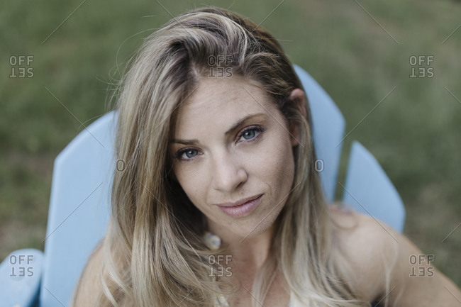 Close up of a blonde woman sitting in an Adirondack chair looking at camera