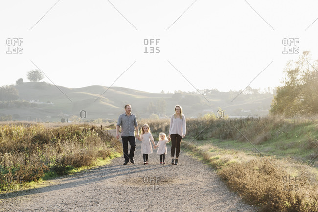 Mom and dad walking with two young daughters on a rural path at sunset