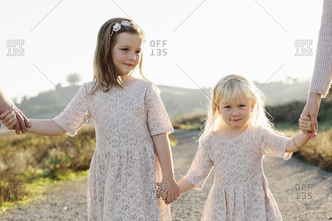 Sisters holding hands with each other and parents as they walk on a rural path at sunset