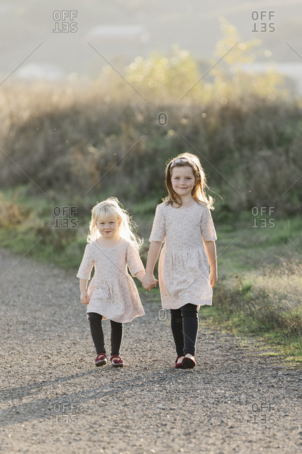 Sisters holding hands as they walk on a rural path at sunset
