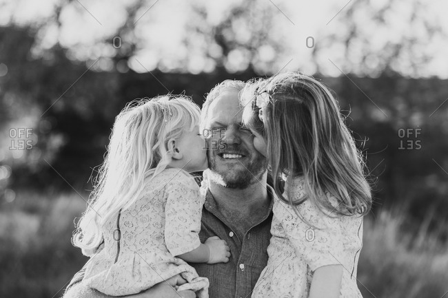 Two young daughters kissing dad's cheeks in black and white