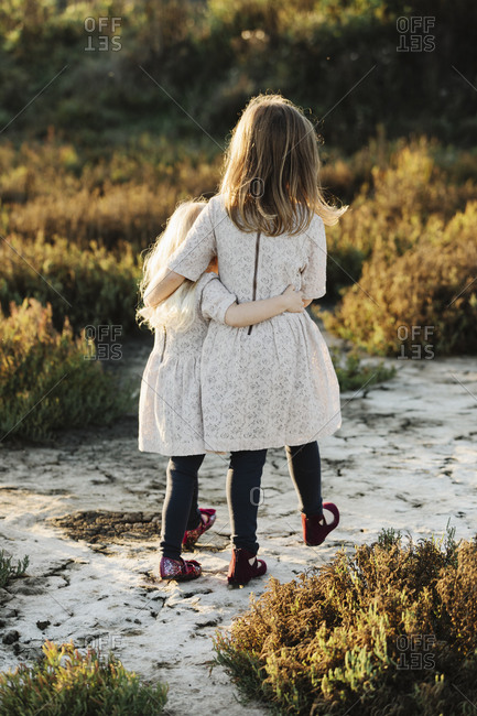 Sisters walking on a rural path at sunset