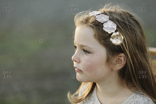 Portrait of a young girl wearing a white floral headband