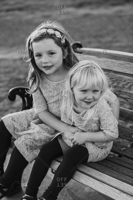 Sisters hugging on a bench in black and white