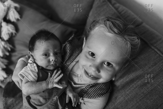 Big sister holding baby brother in black and white
