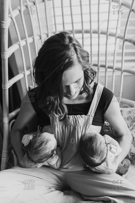 Mom breastfeeding her twin baby boys in black and white