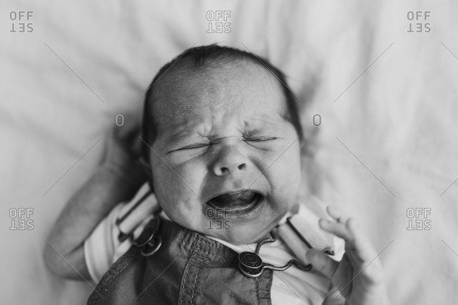 Baby boy wearing overalls lying on bed crying in black and white