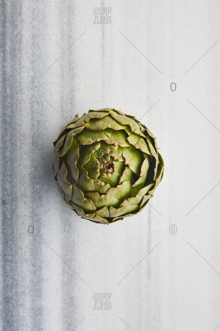 Overhead view of an artichoke on a marble surface