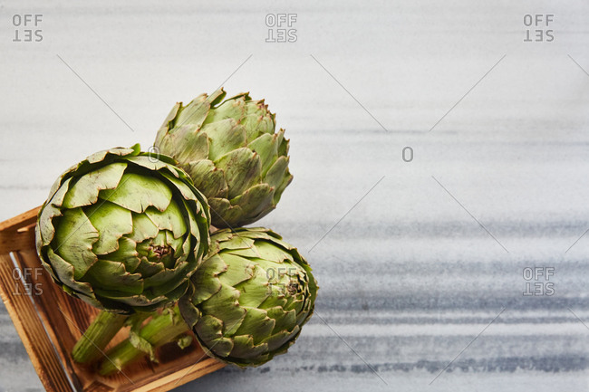 Group of natural artichoke in a crate on a marble surface