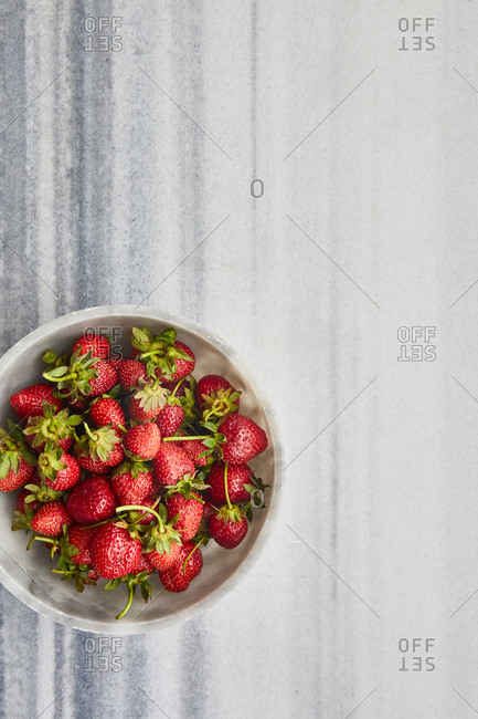 Organic strawberry in a bowl on white marble surface