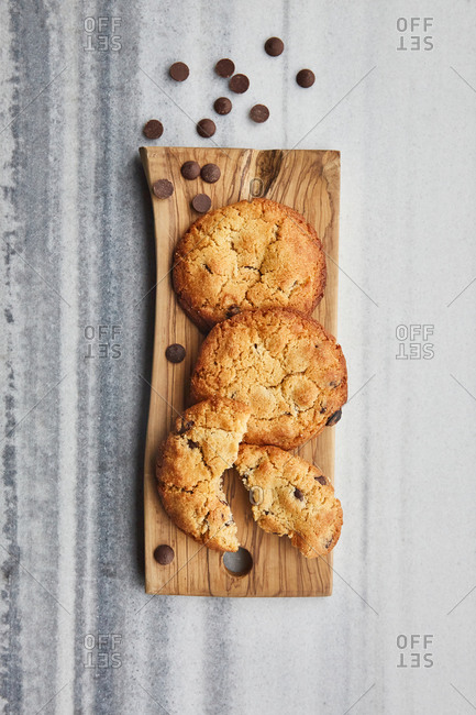 Chocolate chip cookies on a wooden board on a marble surface