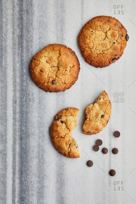 Overhead view of cookies and chocolate chips on a marble surface
