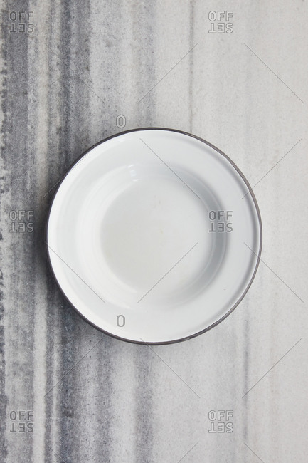 Empty white enamel plate on a marble surface