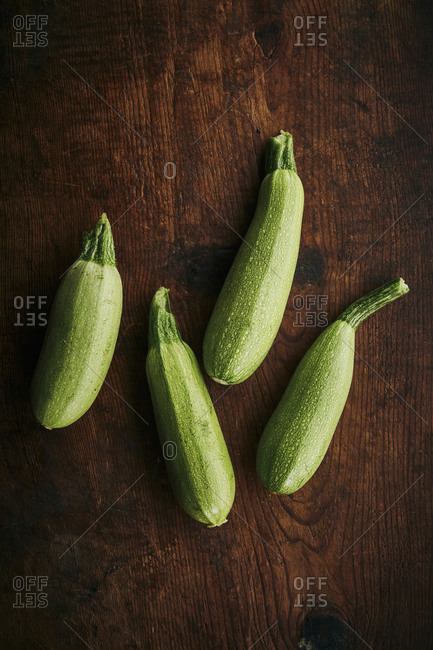 Four fresh zucchini on a wooden rustic surface