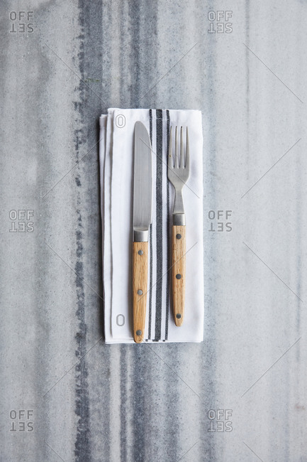 Fork and knife with kitchen napkin on a marble surface